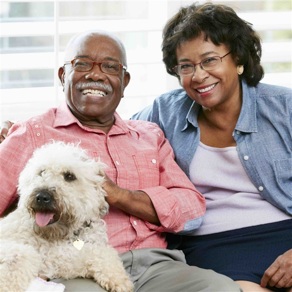 Couple smiling with dog on lap